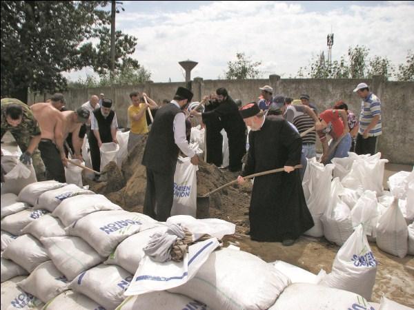 Preoţi şi credincioşi ai Protoieriei Tecuci ajutând la construirea digului din Galaţi